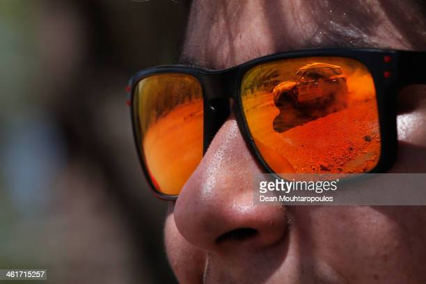 A local fan watches Nasser AlAttiyah of Qatar and Lucas Cruz of Spain for MINI compete as seen in the reflection of his glasses during Day 6 of the...