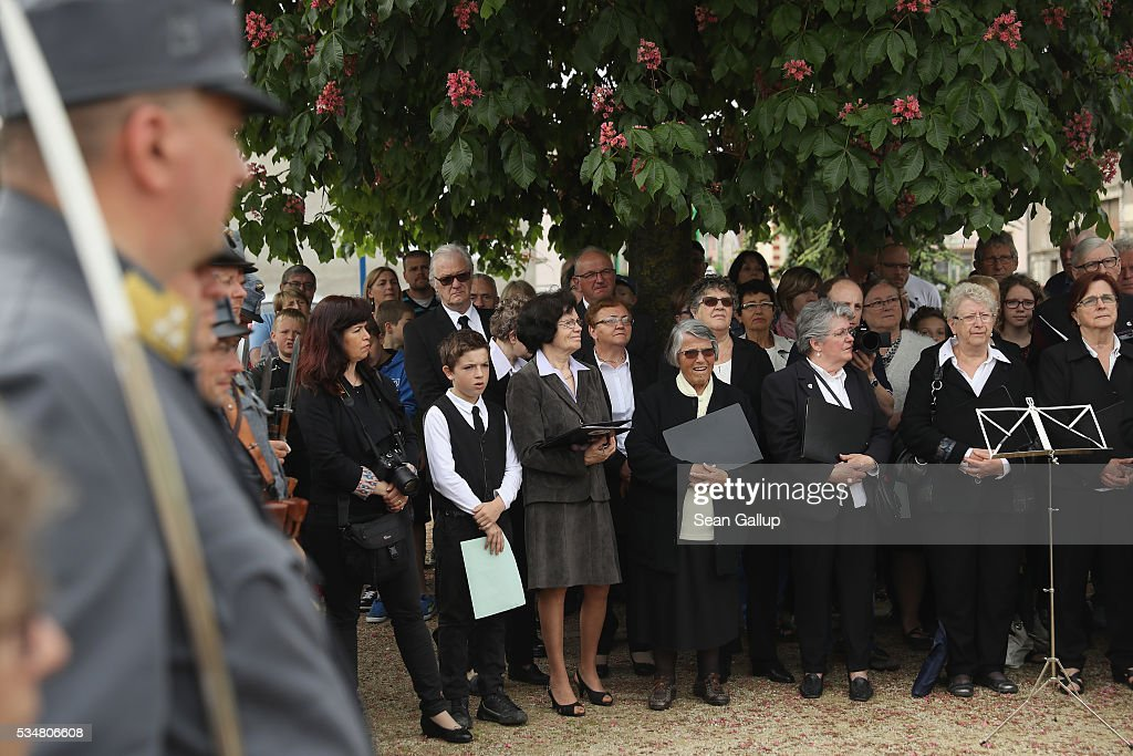 A local female choir as well as history reenactors dressed as World War I Austro-Hungarian soldiers attend a commemoration ceremony at a World War I memorial in Haudainville village on May 28, 2016 near Verdun, France. The governments of France and Germany will commemorate the 100th anniversary of the World War I Battle of Verdun with ceremonies tomorrow. Approximately 300,000 soldiers lost their lives in the 10-month campaign that was among the most grueling battles of World War I.