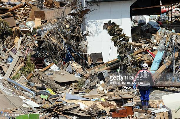 A local firefighter walks among the debris in Ofunato city Iwate prefecture on April 15 2011 Japan's seismologists were so entrenched in outdated...