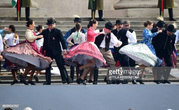 Local folk dancers perform prior to the speech of the Hungarian Prime Minister Viktor Orban in front of the National Museum of Budapest on March 15...