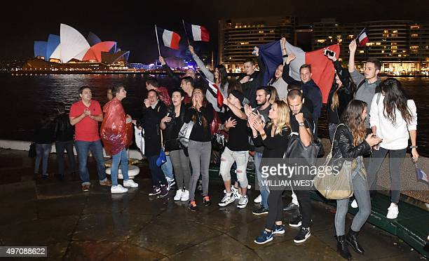 Local French youths sing the national anthem in front of the iconic sails of the Sydney Opera House lit in red white and blue resembling the colours...