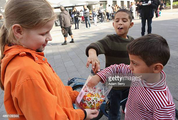 Local girl Lea gives lollipops to Syrian refugee children at a welcome festival for migrants on September 19 2015 in the Karolinenviertel...