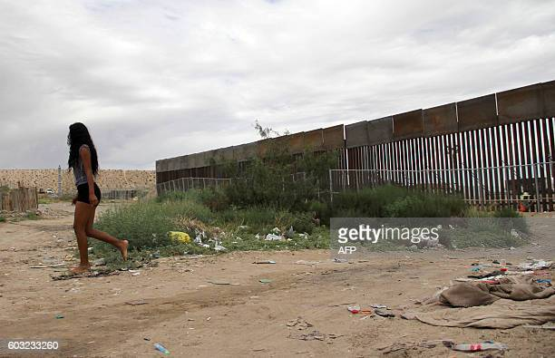 A local girl walks near the higher new metal wall installed by US workers to replace fencing along the border between Ciudad Juarez and Sunland Park...