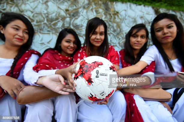Local girls pose for photographs while holding a matchball during the FIFA U17 World Cup India 2017 tournament on October 10 2017 in Guwahati India