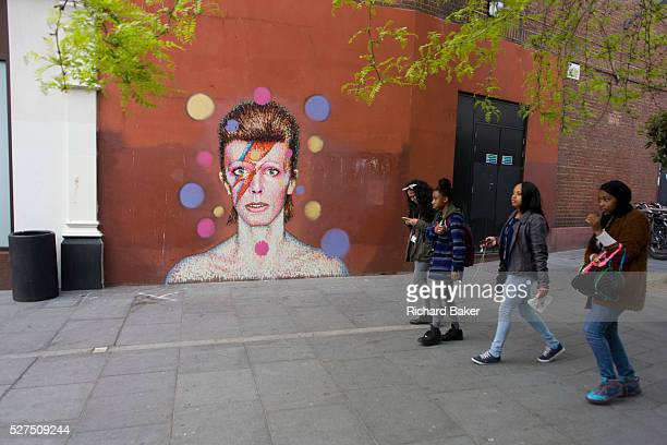 Local girls walk past the mural of iconic musician and singer David Bowie has appeared on the wall of Morleys department store in Brixton Lambeth...