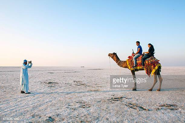 A local guide taking picture of tourists astride a camel in the Great Rann of Kutch a seasonal salt marsh located in the Thar Desert of Gujarat India...