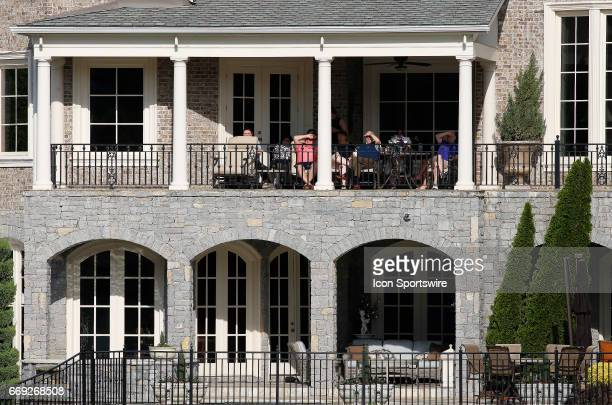 Local homeowners watch the 18th green during the final round of the Mitsubishi Electric Classic tournament at the TPC Sugarloaf Golf Club Sunday...