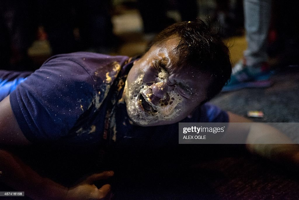 A local Hong Kong journalist collapses in agony after being hit in the face with pepper spray by police in the Mongkok district of Hong Kong on...