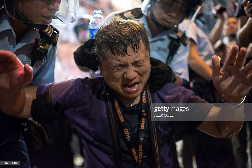 A local Hong Kong journalist hit in the face with pepper spray by police is helped up by officers in the Mongkok district of Hong Kong on October 17...