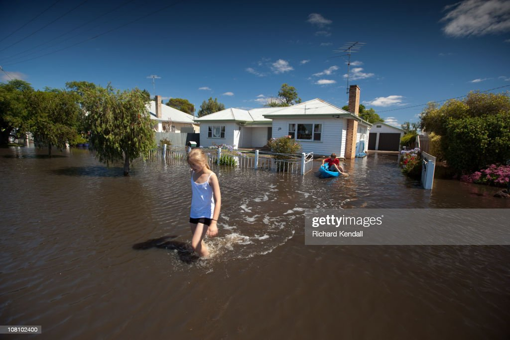 Local Horsham kids navigate through a flooded street on January 18, 2011 in Horsham, Australia. Residents and emergency crews sandbagged properties and evacuations were ordered in the town in preparation for the worst flooding in over 200 years. A relief centre has been set-up in at Horsham Town Hall and emergency crews are on-site as the Wimmera River water level continues to rise.