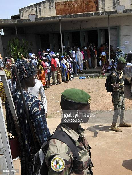 A local hunter called Dozo along with soldiers stands guard on October 31 2010 at a polling station in Bouake Voters turned out in large numbers in...