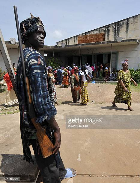 A local hunter called Dozo stands guard on October 31 2010 at a polling station in Bouake Voters turned out in large numbers in key cities in Ivory...
