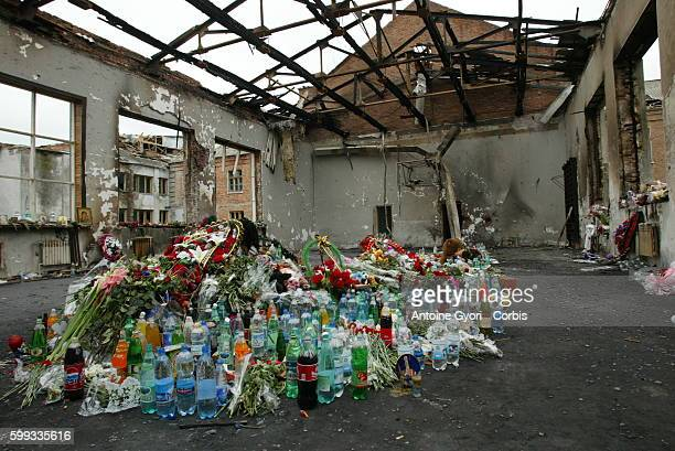 Local inhabitants leave flowers and bottles of water and soda in memory of the Beslan school siege victims in what remains of the charred gymnasium...