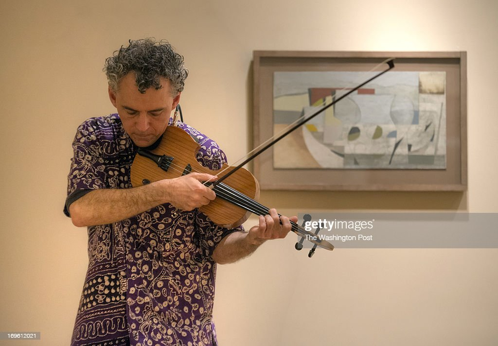Local jazz violinist David Schulman practices for the upcoming family n fun jazz day at the Phillips gallery, where he will be interpreting musically some of the art on May, 07, 2013 in Washington, DC. The work behind him is Still Life (Winter), November 3, 1950, by Ben Nicholson.