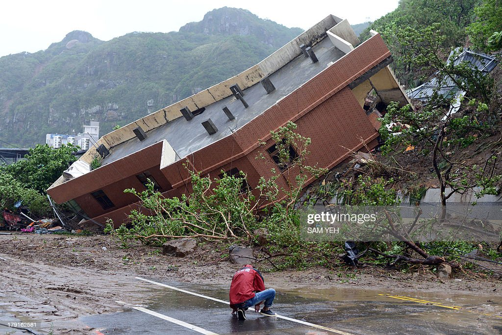 A local journalist stops in front of a building damaged after heavy rains hit Taiwan's northern city of Keelung on September 1, 2013. Tropical Storm Kong-Rey pounded Taiwan, leading to widespread flooding in the south that left three people dead and caused more than 11 million USD in agricultural damage, the government said. AFP PHOTO / Sam Yeh