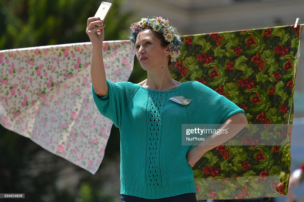 A local lady wears a wreath made from flowers, and takes a souvenir selfy, as many people of all age gathered in Tbilisi center for a popular celebrations, as Georgia Celebrates its Independence Day commemorating the adoption of the Act of Independence in 1918, that outlined the main principles of the nation's democratic development and formed a first-ever republic under German and British protection, but was then invaded by Bolshevik Russia and absorbed into the Soviet Union. On April 9, 1991, Georgia once again regained its independence. This year Georgia celebrates the 25th Anniversary since the restoration of its independence. Tbilisi, Georgia, on Thursday 26 May 2016.