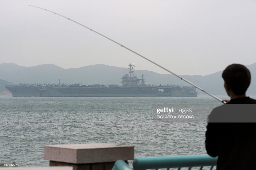 A local man fishes as the aircraft carrier USS George Washington sails out of Hong Kong on November 12, 2013 to join the rescue and relief operations in the Philippines following Super Typhoon Haiyan. US and British warships were deployed on November 12 to the typhoon-ravaged Philippines where well over 10,000 people are feared dead and countless survivors are begging for help in rain-soaked wastelands. Four days after Super Typhoon Haiyan destroyed entire coastal towns in mostly poor central islands with record winds and tsunami-like waves, the magnitude of the disaster continued to build with almost unimaginable horror.