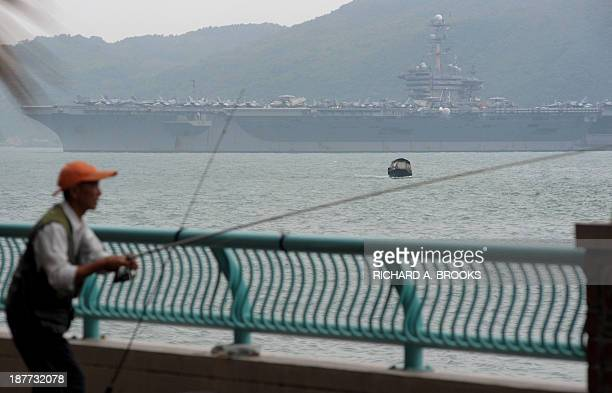 A local man fishes as the aircraft carrier USS George Washington sails out of Hong Kong on November 12 2013 to join the rescue and relief operations...