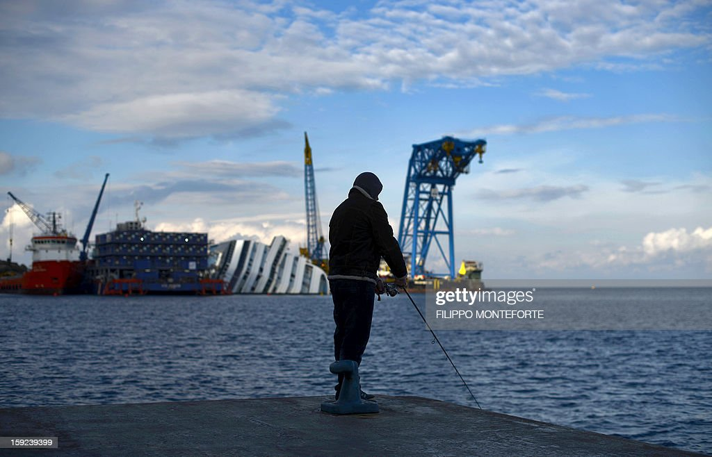 A local man fishes as the Costa Concordia cruise ship is seen in the background laying aground on January 10, 2013 on the Italian island of Giglio. A year on from the Costa Concordia tragedy in which 32 people lost their lives, the giant cruise ship still lies keeled over on an Italian island and its captain Francesco Schettino has become a global figure of mockery.