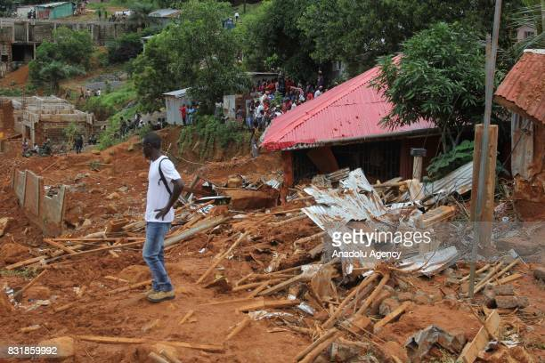 A local man is seen on a wreckage at Regent region of Freetown after landslide struck the capital of the west African state of Sierra Leone on August...