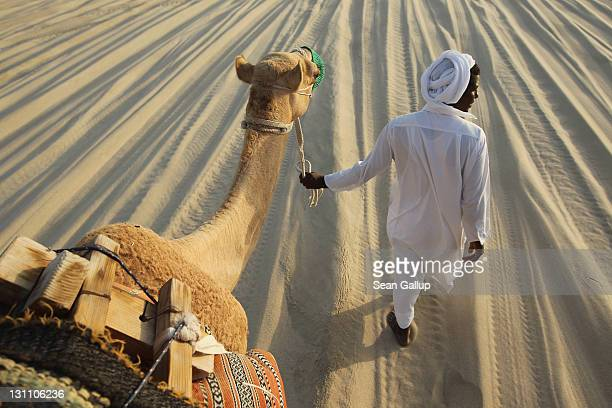 A local man leads tourists riding camels on desert dunes that lead to the Khor al Adaid inlet of the Persian Gulf on October 30 2011 near Umm Sa'id...