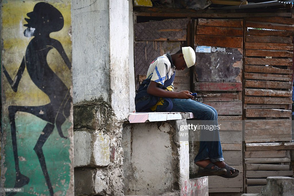 A local man looks at his cellular phone in Stone Town in Zanzibar on January 7, 2013. AFP PHOTO / GABRIEL BOUYS
