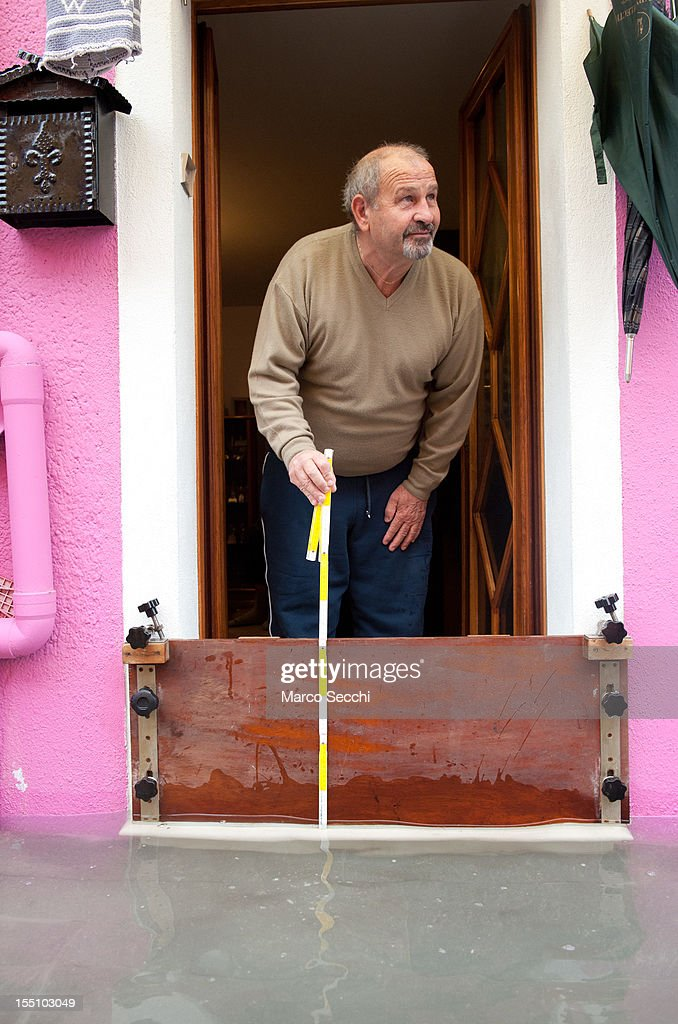 A local man measures the rising water in Burano on November 1, 2012 in Venice, Italy. More than 59% of Venice has been been left flooded, after the historic town was hit by exceptionally high tides. The sea level rose above 140cm overnight was expected to remain above critical levels for about 15 hours.