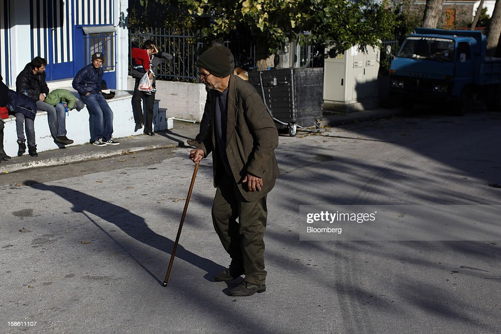 A local man passes afghan immigrants resting in front of a store hours after they landed on the island of Lesbos' northern coast in Mantamados, Greece, on Saturday, Dec. 8, 2012. In recent months, Lesbos has become a hot spot for migrants as Greece struggles to cope with waves of refugees from Middle Eastern conflict even as it reels from economic crisis at home. Photographer: Kostas Tsironis/Bloomberg via Getty Images