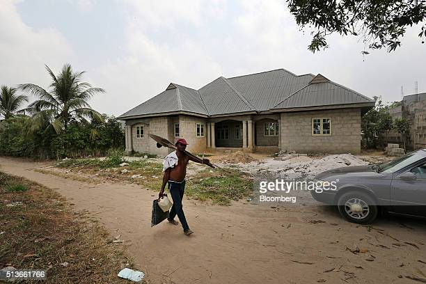 A local man passes an unfinished new house under construction with compensation money paid to the local community by the Royal Dutch Shell Plc oil...