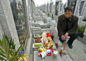 A local man pays respects at a grave in a cemetery near Shanghai 03 April 2004 on the eve of Tombsweeping Festival or Qingming Millions of people...