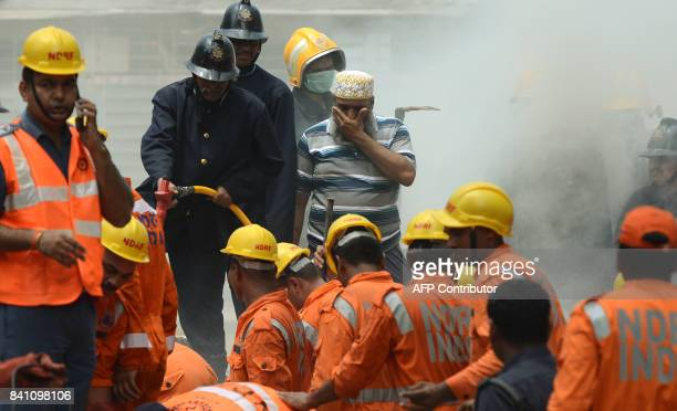 A local man reacts as rescue workers look for survivors at the site of a building collapse in Mumbai on August 31 2017 At least three people died and...