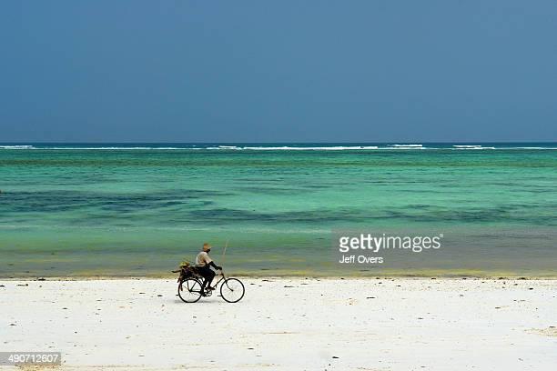 Local man seen cycling along the coastline of a beach in Zanzibar Tanzania