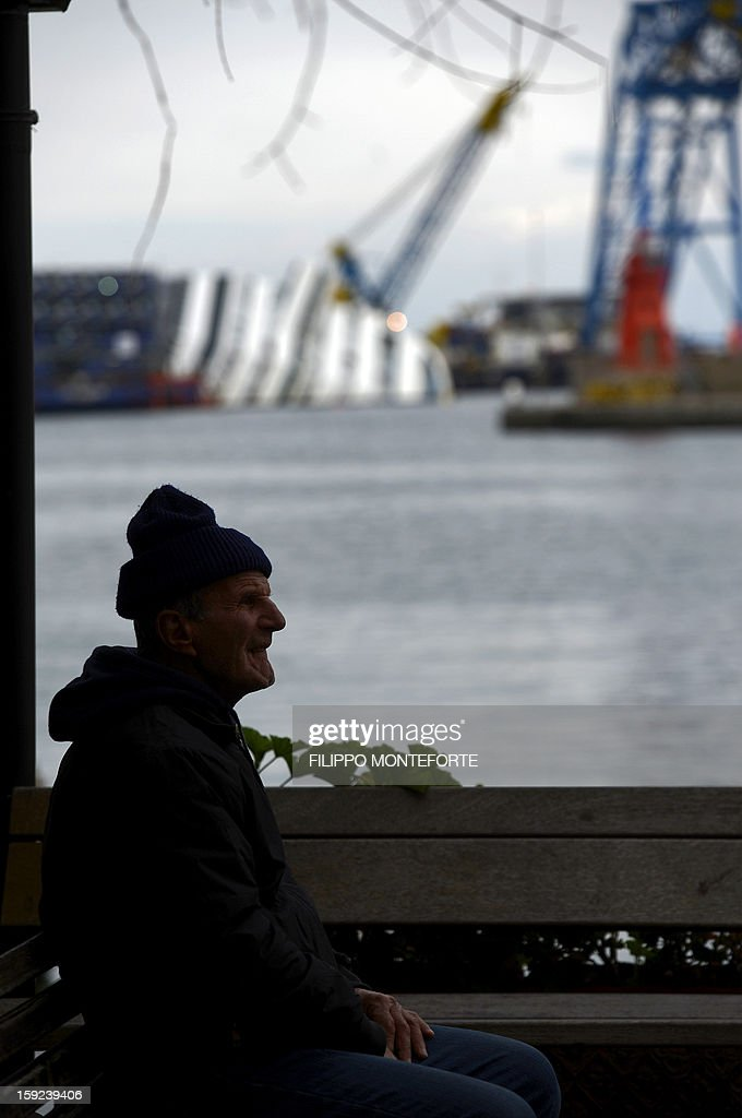 A local man sits in the village as the Costa Concordia cruise ship is seen in the background laying aground on January 10, 2013 on the Italian island of Giglio. A year on from the Costa Concordia tragedy in which 32 people lost their lives, the giant cruise ship still lies keeled over on an Italian island and its captain Francesco Schettino has become a global figure of mockery.