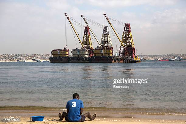 A local man sits on the beach beyond heavy lifting shipping cranes on barges moored off the shoreline in Luanda Angola on Friday Nov 8 2013 Angola...