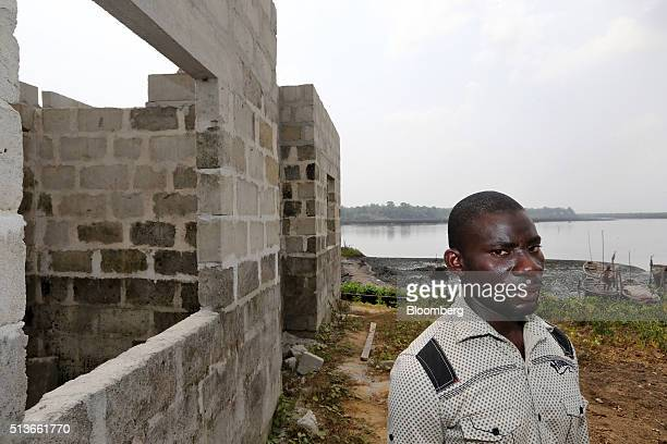 A local man stands beside an unfinished new house under construction with compensation money paid to the local community by the Royal Dutch Shell Plc...