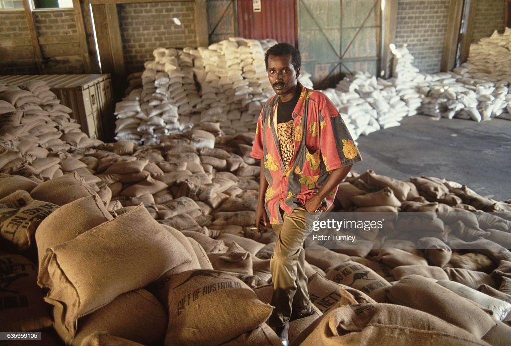 A local man stands in a makeshift warehouse with the sacks of food sent as aid packages during 'Operation Restore Hope' In the 1980s a civil war...