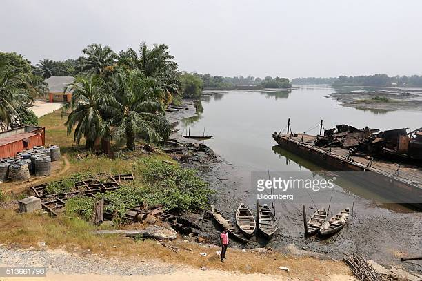 A local man stands near fishing boats in an oil polluted creek in Bodo Nigeria Wednesday Jan 13 2016 Twenty years after the oilpollution crisis in...
