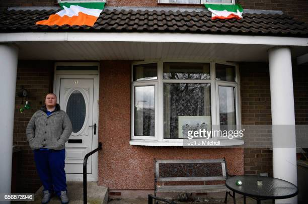 A local man stands outside a house with a photo of the late Martin McGuinness displayed in the window as he watches the funeral on a large screen on...
