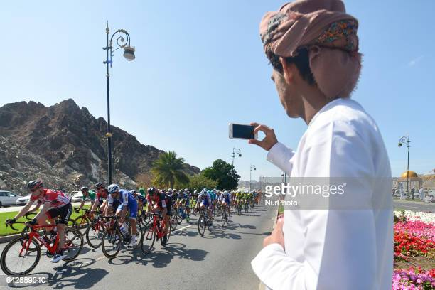 A local man takes a photo of the passing by peloton of riders during the sixth and final stage a 1305km from The Wave Muscat to Matrah Corniche at...