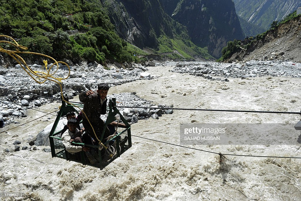 A local man throws a rope as he and others riding a gondola cross the Alaknanda river from the Hemkund Sikh temple to Govindghat following flash floods in Uttarkhand state on June 30, 2013. More than 100,000 mainly pilgrims and tourists have been evacuated from the disaster zone while some 4,000 remain in relief camps after the flash floods and landslides that hit the state on June 15.