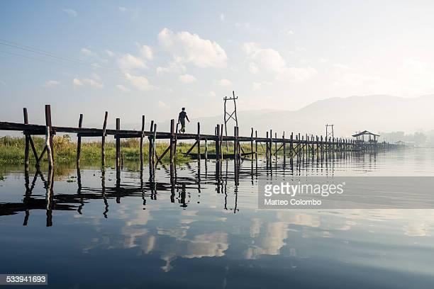 Local man walking on wooden bridge, Myanmar