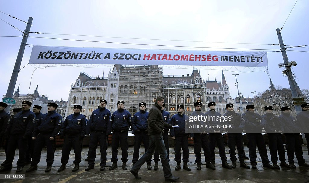 A local man walks in front of a line of policemen, under a gigant banner with a text 'Welcome the march of the hunger of the Socialists' power' at the parliament building as the participants of the 'Hunger march' and their sympathizers shout some anti-government slogans near the Hungarian parliament building in Budapest on February 11, 2012 during the first meeting of the Hungarian Parliament this year. Demonstrators, who arrived on foot from several Hangarian cities to protest against the Hungarian government's economy and financial policy. AFP PHOTO / ATTILA KISBENEDEK