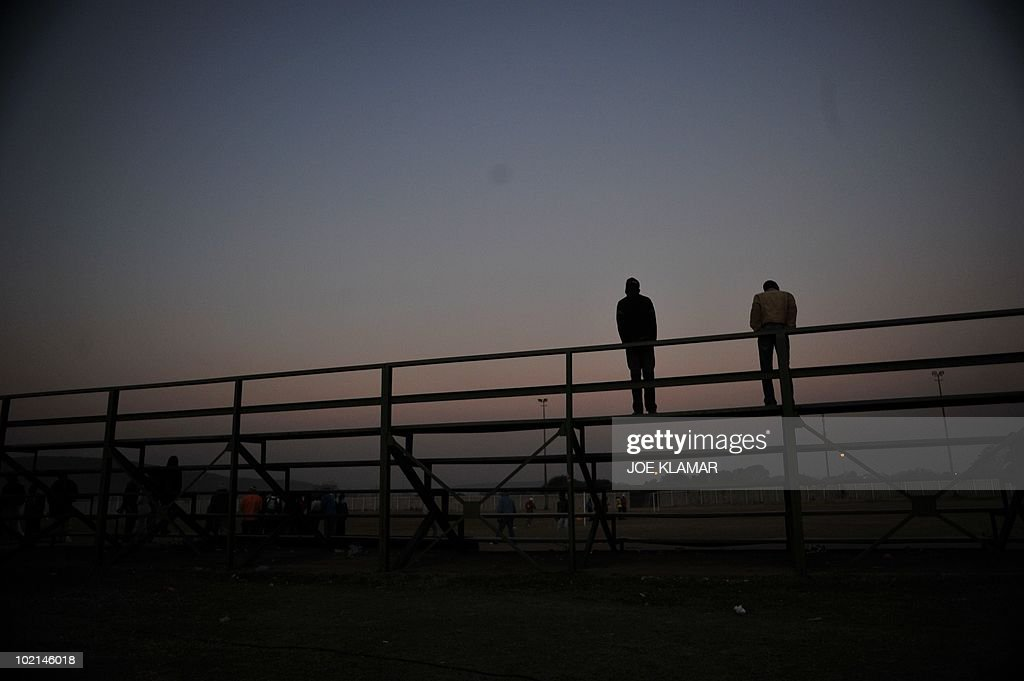 Local man watch their friends play soccer at Mamelodi township in Pretoria on June 16, 2010 during the 2010 World Cup football tournament in South Africa.