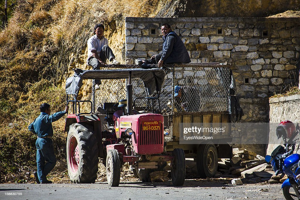 Local men and worker on a tractor on November 18, 2012 in Bumthang, Bhutan.