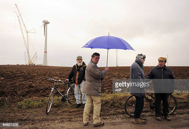 Local men are pictured in front of Estinnes wind turbine park in Bray some 60 kms southwest of Brussels on February 5 2009 The Estinnes wind farm...