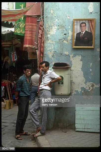 Local men chatting by Pres Ben Ali's portraitgraced wall in fore of colorful warelined souk