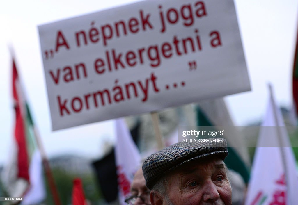 A local men listens to the former Hungarian premier Gordon Bajnai (not pictured) as activists and sympathizers of Hungarian 'Szolidaritas' Movement hold their national flags an a banner with a text, 'The people have a right to kick their government out' in Budapest on September 29, 2013 during their anti-government demonstration to protest against the financial and economic policy of the Orban's government.
