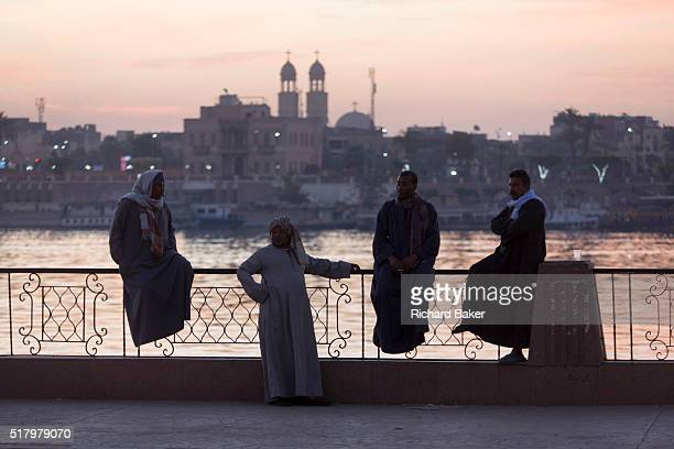 Local men on the West Bank of the river Nile talk at dawn on railings overlooking the city of Luxor Nile Valley Egypt The waterfront is a meeting...