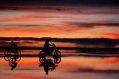 Local men ride their motorbike and bicycle as the sun sets over the Salar de Uyuni of Uyuni Salt Flat during Day 7 of the 2014 Dakar Rally on January...
