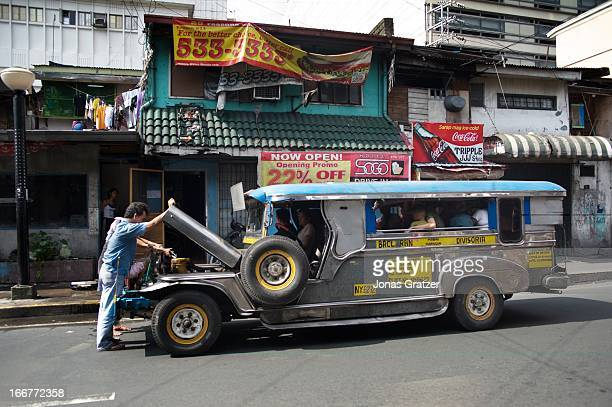 A local minibus called a Jeepney makes an unscheduled breakdown stop as the driver checks the engine